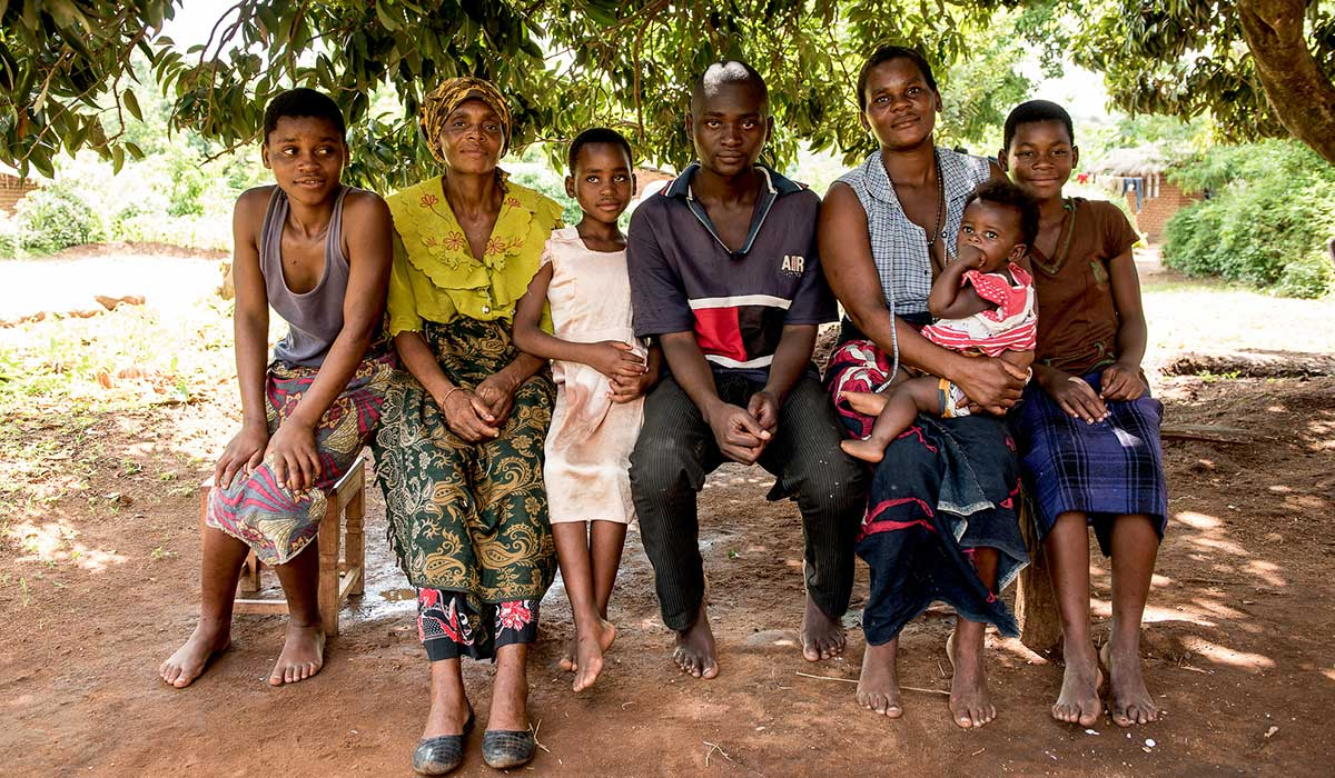Esterei and her family sat in a line - she's a member of CBM's partner Mental Health Users and Carers Association (MEHUCA) local committee, in Malawi.