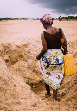 A woman facing away from the camera is wearing a black top and a patterned skirt. She is leaning over into a deep ditch in the sand with water at the bottom and carries a yellow jerry can.