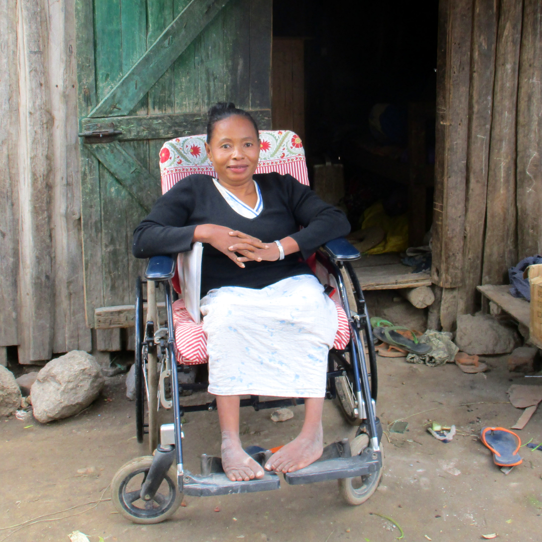 A woman wearing a black top and white skirt sits in her wheelchair outside, in southern Madagascar.