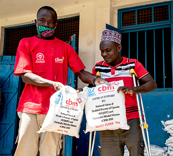 Umaru (right) receives maize flour and rice as part of CBM and NUDIPU's COVID-19 response in Uganda.