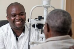Dr Theophile Tuyisabe. examining a patient with cataracts