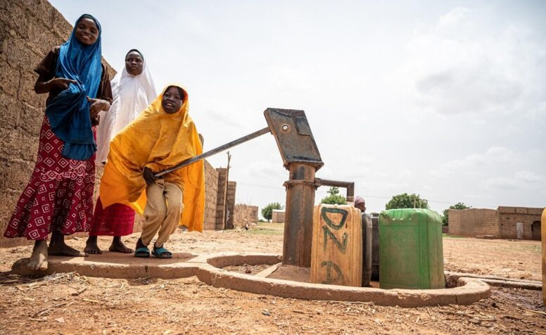 Girls drawing water from a pump, Nigeria