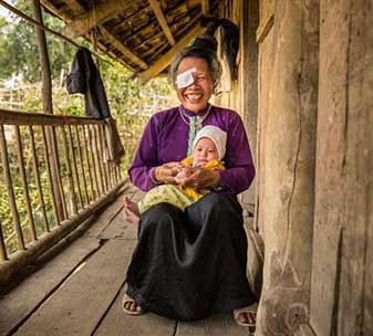 Pom sitting on her porch at home, holding her baby grandsonn her porch at home, holding her baby grandson