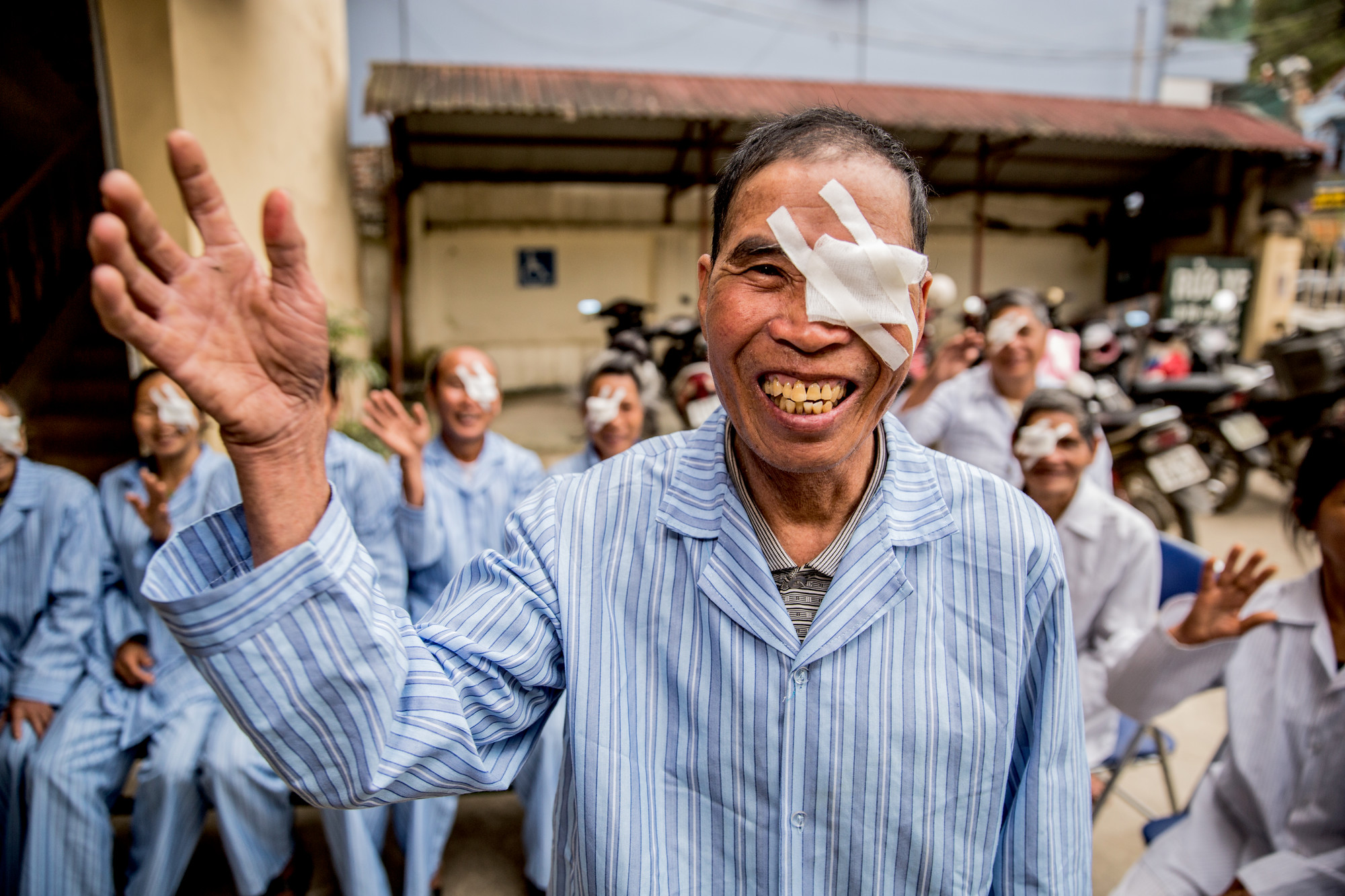 Khut smiling and waving, in a blue hospital gown with an eye patch over his left eye