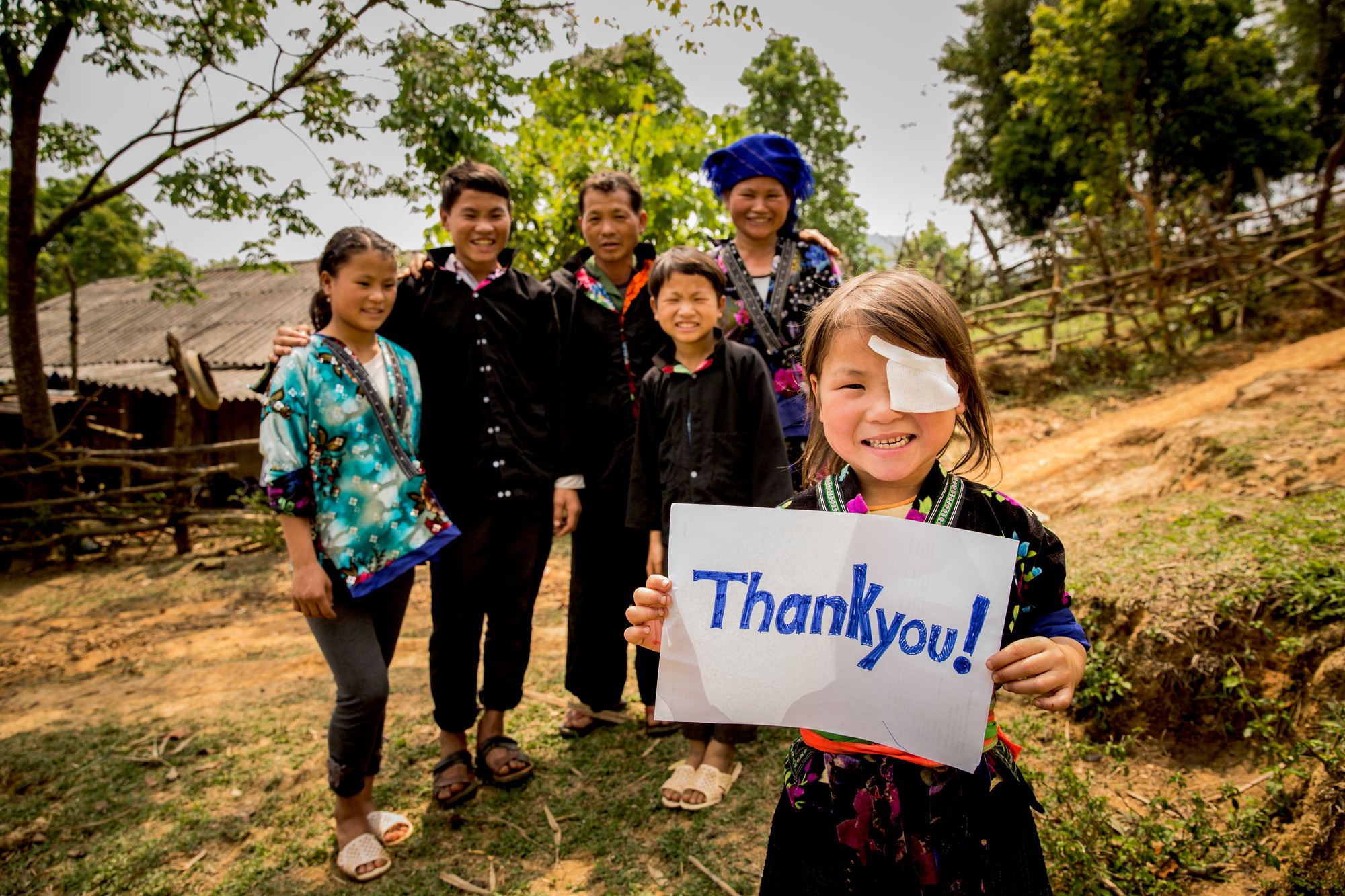 Nhung holding a Thank You sign and smiling, with her family standing behind her.