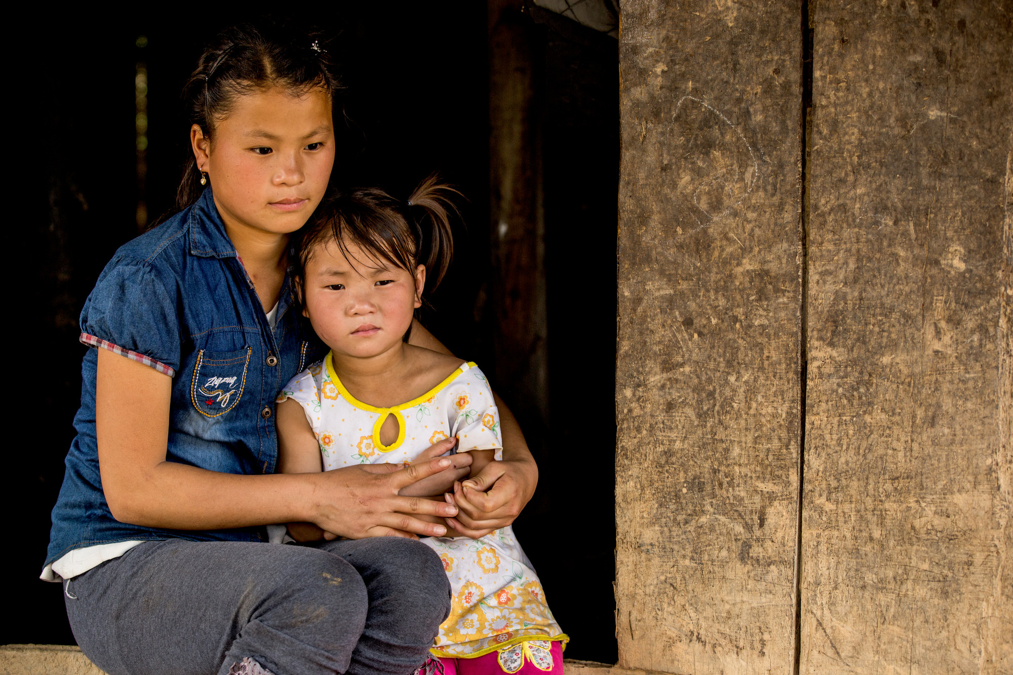 Nhung sitting outside her home with her sister La