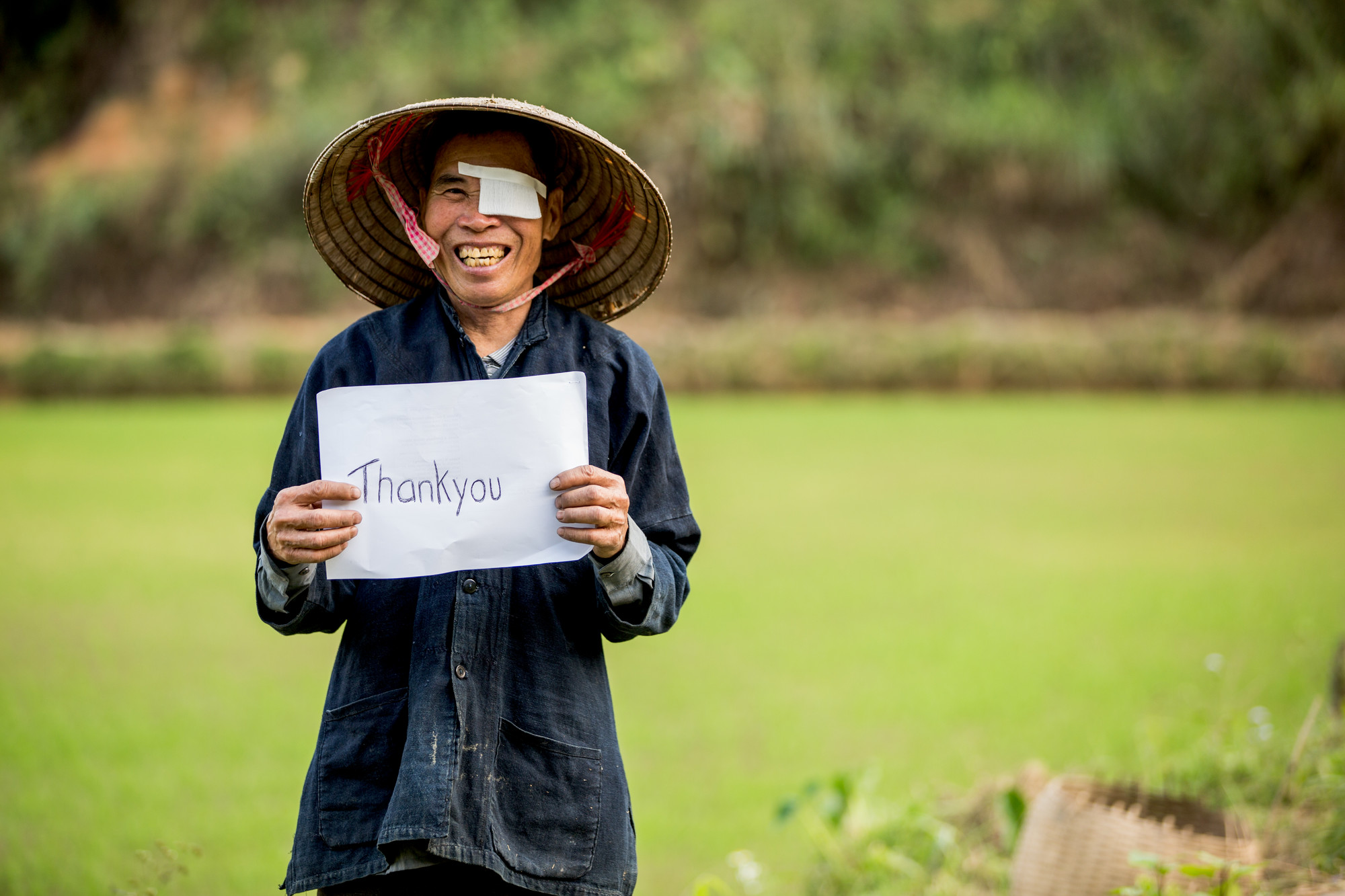 Khut in his field at home, wearing a hat and holding a Thank You sign.