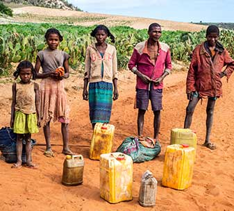 People in southern Madagascar, standing on a sandy road with plastic water containers on the ground in front of them