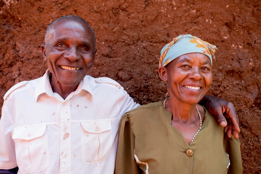 Just from Tanzania, smiling and standing with his arm around his wife.