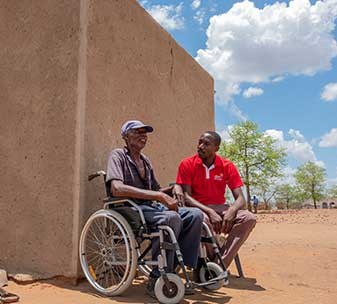 CBM Zimbabwe Emergency Response Team member Allen with Ezekiel, 62, in his new wheelchair at his home in a food-insecure area of Chiredzi, Zimbabwe.