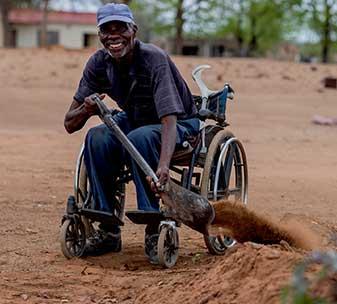 Wheelchair user Ezekiel (62) digs a rainwater channel near his home in Zimbabwe.