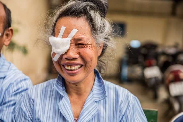 Pom at hospital, smiling with an eye patch over her right eye.