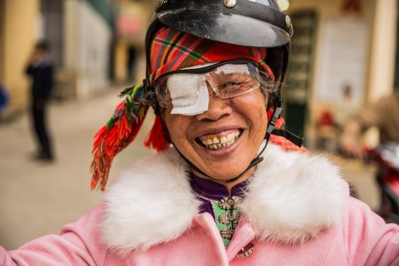 Pom from Vietnam, driving a motorcycle and smiling, with an eye patch over her right eye.