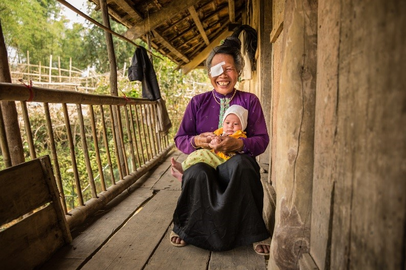 Pom sitting on her porch at home, holding her baby grandson
