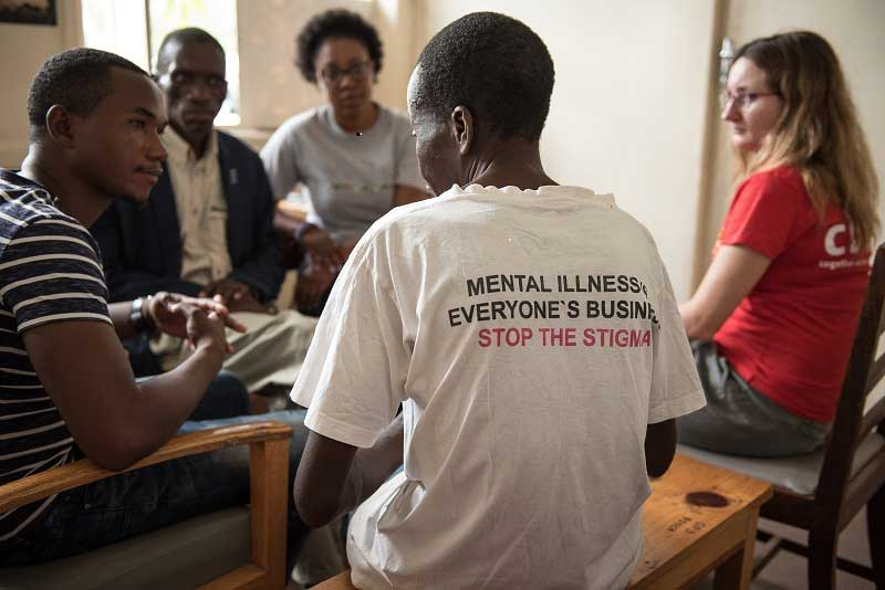 Mphatso attending a counselling session - MeHUCA committee member wear a t-shirt saying 'Mental illness. Everyone's business. Stop the stigma'.